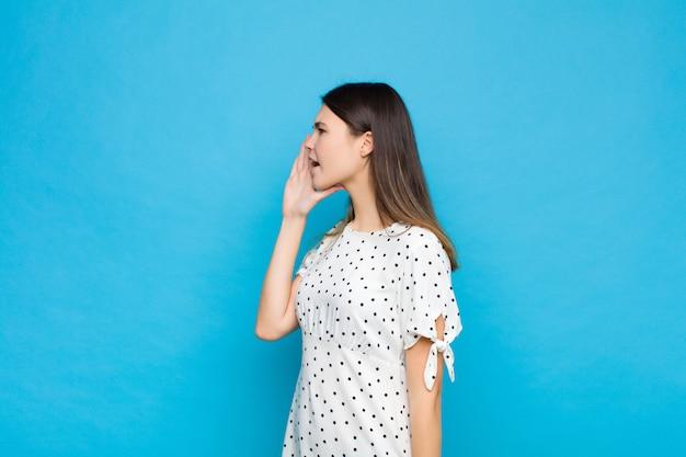 若いきれいな女性の縦断ビュー、幸せそうに見えて興奮して、叫び、青い壁の側にスペースをコピーするための呼び出し