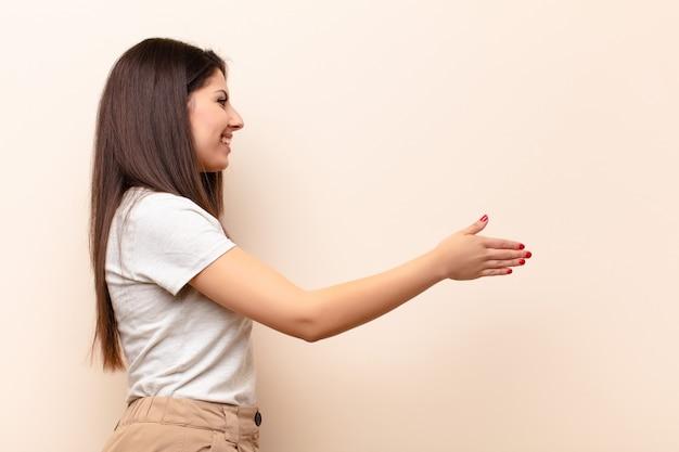 Молодая красивая женщина улыбается, приветствуя вас и предлагая дрожание рук, чтобы закрыть успешную сделку, концепция сотрудничества