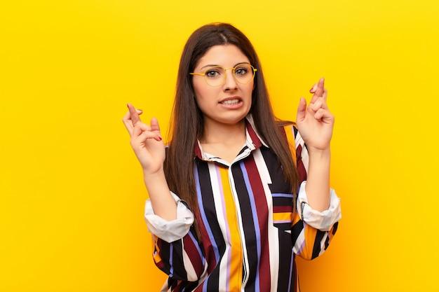 Молодая красивая женщина с тревогой скрещивает пальцы и надеется на удачу с обеспокоенным взглядом на желтую стену