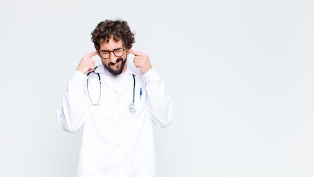 Молодой врач мужчина выглядит злой, стресс и раздражение, прикрывая оба уха оглушительным шумом, звуком или громкой музыкой на фоне копией пространства