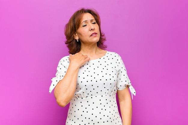 ストレス、不安、疲れ、欲求不満、シャツの首を引っ張る、紫の壁の問題で欲求不満に見える中年女性