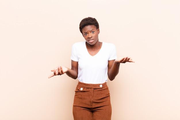Молодая симпатичная черная женщина чувствует себя невежественной и растерянной, не уверенной, какой выбор или вариант выбрать, задается вопросом