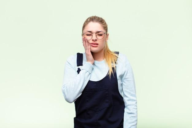 若いブロンドの女性が頬を押しながら痛みを伴う歯痛に苦しんで、気分が悪く、悲惨で不幸になり、平らな壁で歯科医を探している