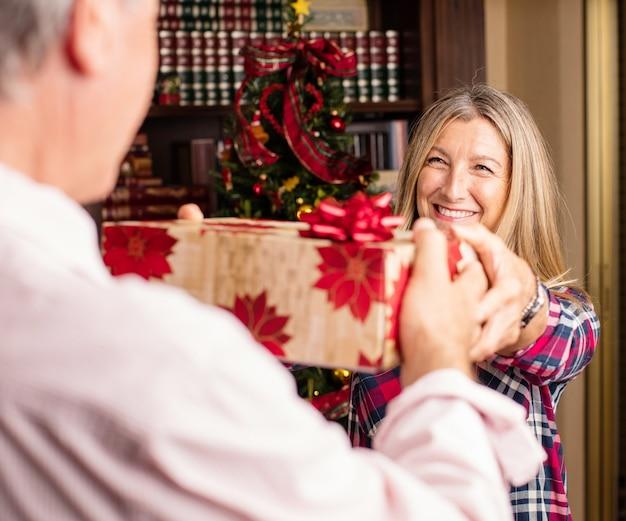 Человек дает подарок женщине