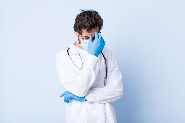 Молодой человек, глядя подчеркнул, стыдно или расстроен, с головной болью, закрыв лицо рукой. концепция коронавируса
