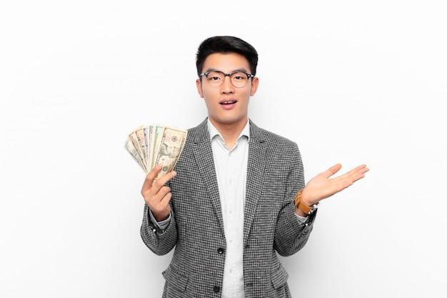 Молодой японец, чувствуя себя счастливым, удивленным и веселым, улыбаясь позитивным настроем, понимая решение или идею. концепция денег