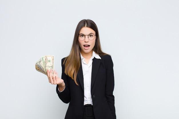 Молодая красивая женщина выглядит очень шокирован или удивлен, глядя с открытым ртом, говоря вау с банкнотами