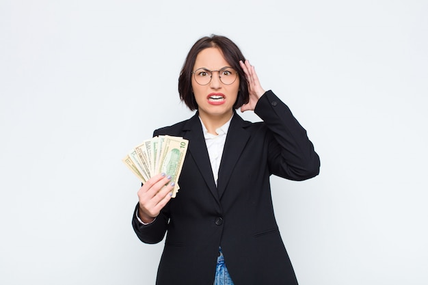 Молодая красивая женщина кричит с поднятыми вверх руками, чувствуя ярость, разочарование, стресс и расстроен счетами