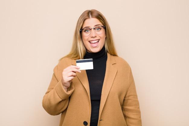 Молодая блондинка выглядит счастливой и приятно удивленной, взволнованной с очарованным и шокированным выражением с помощью кредитной карты