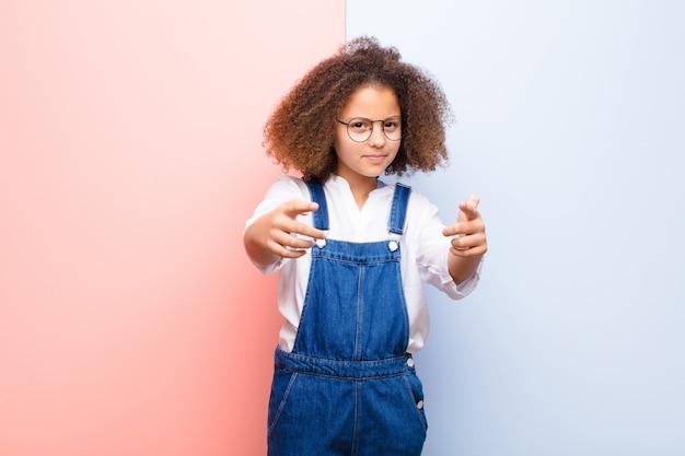 壁を越えてあなたの義務を果たすようにあなたに告げる両方の指と怒っている表情でカメラを前に向けている少女