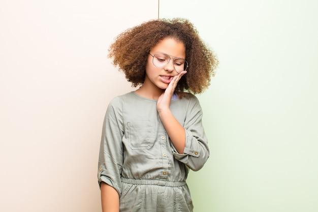 頬を押し、痛みを伴う歯痛に苦しんでいる、病気、悲惨で不幸な感じ、壁越しに歯科医を探している少女