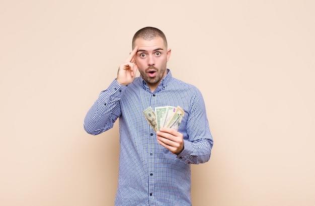 Молодой красавец смотрит удивленно, с открытым ртом, в шоке, понимая новую мысль, идею или концепцию с банкнотами доллара