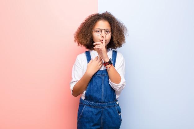 深刻な探しているアフリカ系アメリカ人の女の子と指で横になって沈黙または静かを要求する唇を押して、平らな壁に秘密を守る