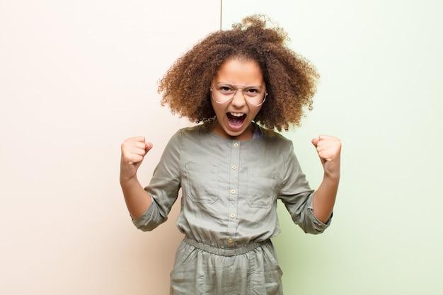 アフリカ系アメリカ人の少女が怒りの表情で、または拳で握りしめられて平らな壁に対して成功を祝って積極的に叫んでいる