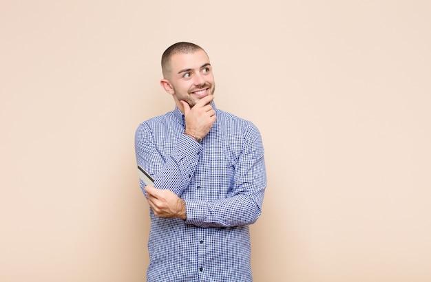 クレジットカードで側にいる幸せそうに笑って、空想にふけったり、疑ったりする若いハンサムな男