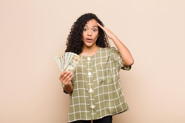 Молодая женщина смотрит удивленно, с открытым ртом, в шоке, понимая новую мысль, идею или концепцию, держа доллар банкноты