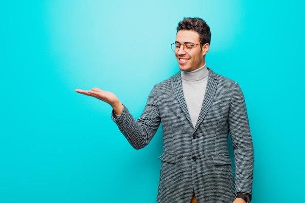 アラビア語の若い男が青い壁に対して側の手で開催されたオブジェクトまたはコンセプトを探して、何気なく幸せと笑顔を感じて