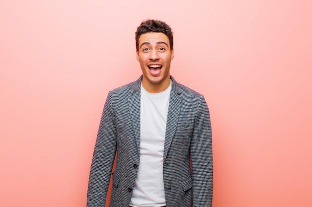 大きく、フレンドリーで、のんきな笑顔で、肯定的なリラックスした幸せなピンクの壁に身も凍るようなアラビアの若者