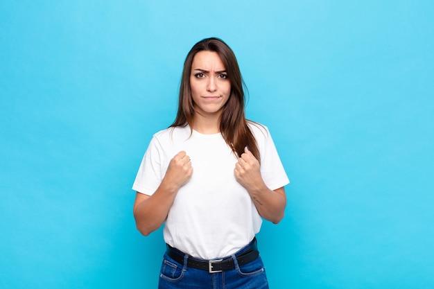 自信を持って、怒って、強くて攻撃的な若いきれいな女性、青い壁に対してボクシングの位置で戦う準備ができている拳で