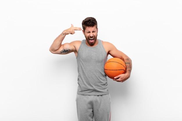 バスケットボールのボールを保持している頭を指している不幸と強調した自殺ジェスチャーを手で銃のサインを作る若いハンサムな男。