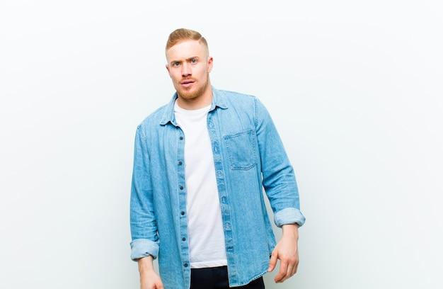 Молодой блондин человек в джинсовой рубашке чувствуя себя шокирован, счастлив, поражен и удивлен, глядя в сторону с открытым ртом на белом фоне