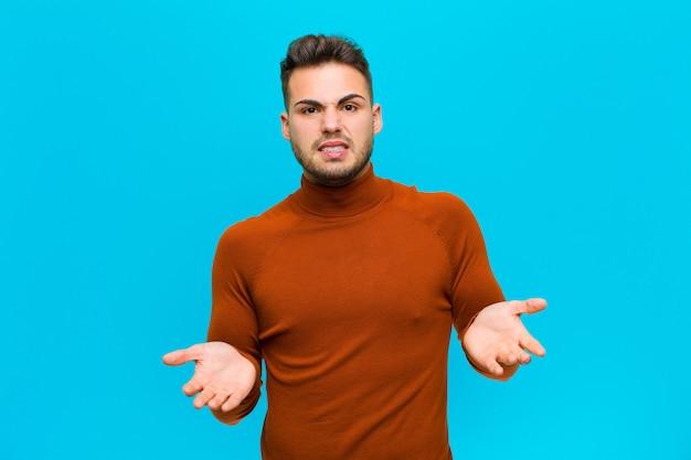Молодой латиноамериканский мужчина чувствует себя невежественным и растерянным, не зная, какой выбор или вариант выбрать, удивляясь на синем фоне
