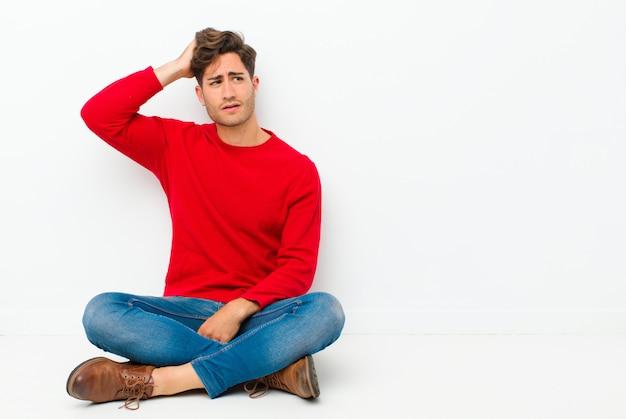 困惑し、混乱し、頭を掻き、床に座っている側を探している若いハンサムな男