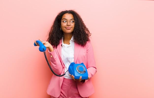 Молодая черная милая женщина с винтажным телефоном на розовой предпосылке стены