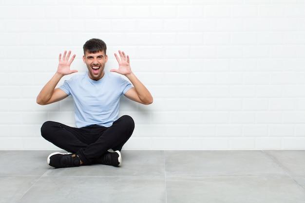 セメントの床に座っている頭の横にある手でパニックや怒り、ショック、恐怖、激怒で叫んでいる若いハンサムな男