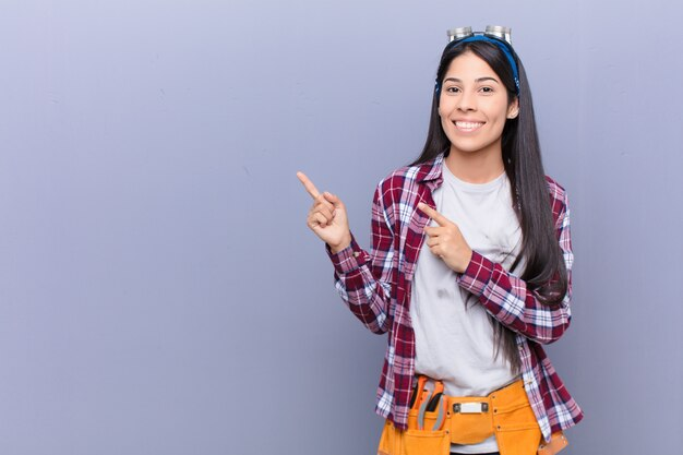 コピースペースでオブジェクトを示す幸せな笑顔と両手で上向きと両側を指している若いラテン女性
