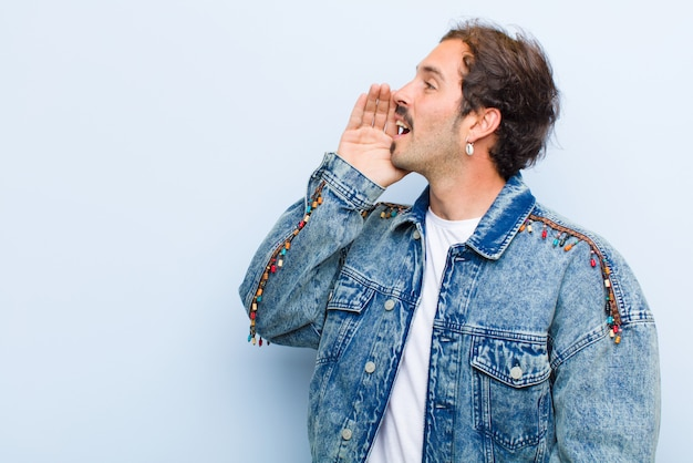 若いハンサムな男のプロフィール、幸せそうに見えて興奮している、叫び、平らな壁に対して隔離された側にスペースをコピーするための呼び出し