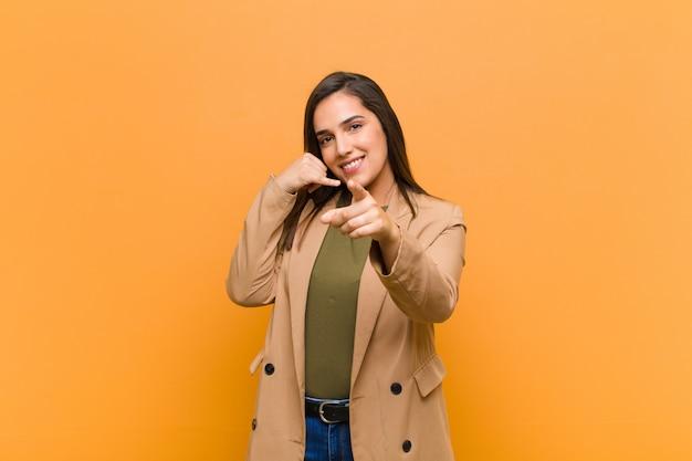 オレンジ色の壁に対して隔離された電話で話している元気な笑顔とカメラを指して後でジェスチャーをかける若いきれいな女性