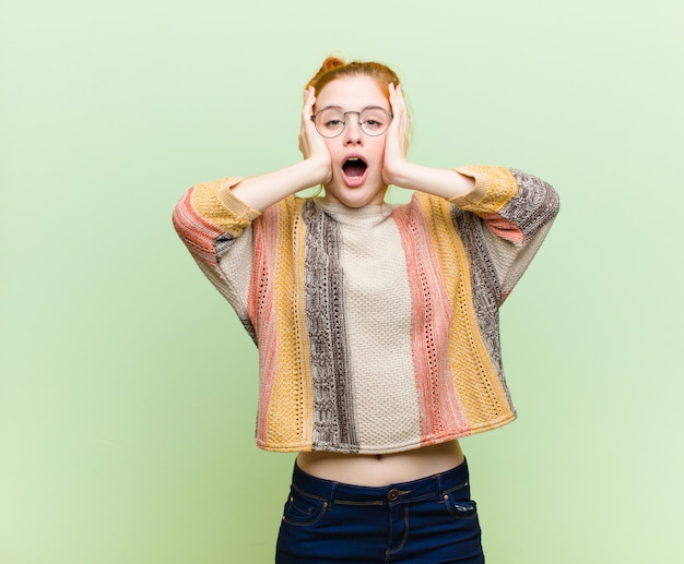 若いかなり赤い頭の女性が不快にショックを受けて、怖がっているか心配して、口を大きく開いて、緑の壁に手で両耳をカバー
