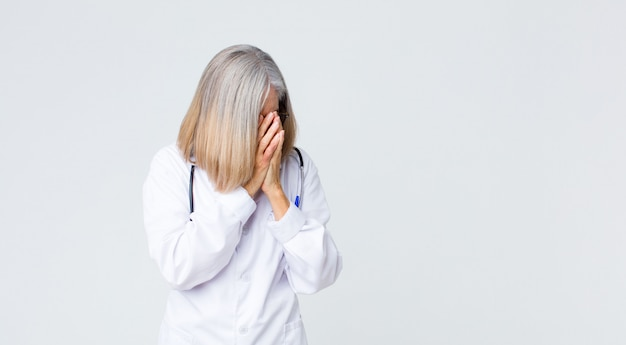 絶望の悲しい、欲求不満な表情、泣いて、側面図で手で目を覆っている中年の医者の女性