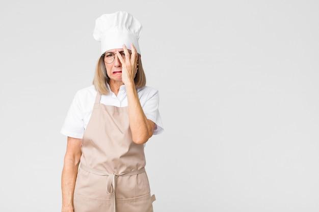 中年のパン屋の女性は、平らな壁に顔を手で持って、退屈で退屈で面倒な作業の後に退屈、欲求不満、眠気を感じています。