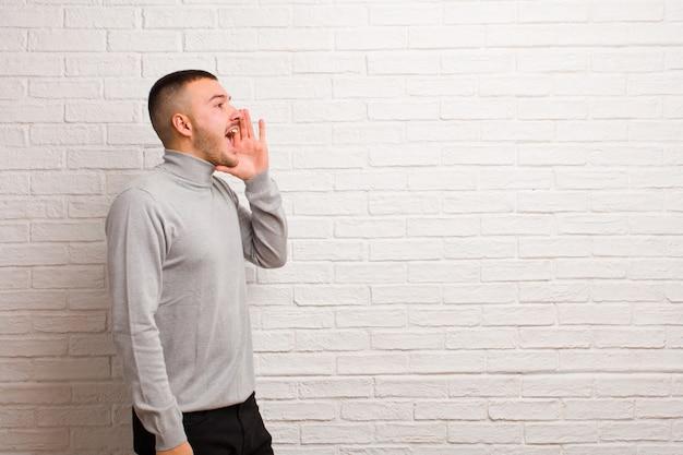 若いハンサムな男の縦断ビュー、幸せそうに見えて興奮している、叫び、平らな背景の側にスペースをコピーするための呼び出し