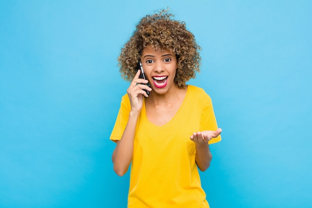 Молодой афроамериканец выглядит отчаянным и разочарованным, подчеркнутым, несчастным и раздраженным, кричащим и кричащим с мобильного телефона