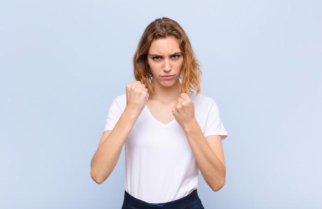 自信を持って、怒って、強くて積極的な探している若いブロンドの女性、拳はフラットな色の壁に対してボクシングの位置で戦う準備ができて