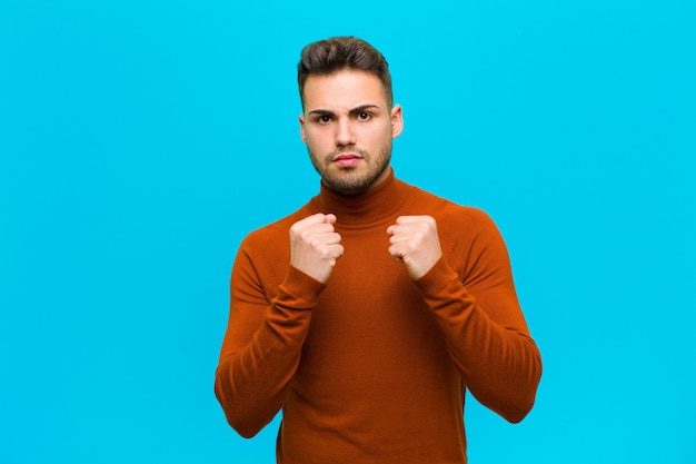 若い男が自信を持って、怒って、強くて積極的、青い背景に対してボクシングの位置で戦う準備ができている拳で