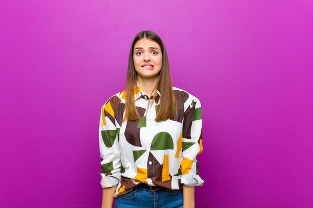 Молодая симпатичная женщина, чувствуя себя невежественной, растерянной и неуверенной в том, какой вариант выбрать, пытаясь решить проблему на фиолетовом фоне
