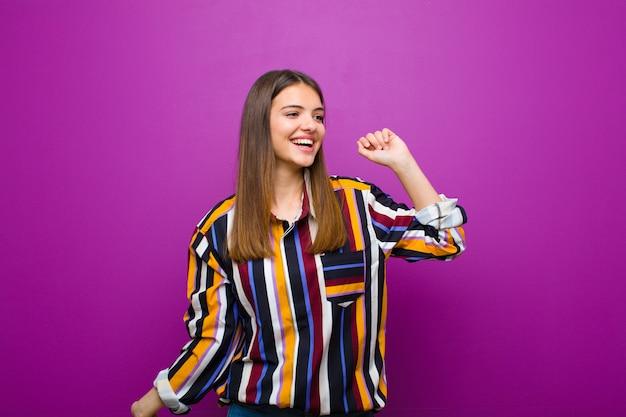 笑顔、屈託のない、リラックスした、幸せな、ダンス、音楽を聴く、紫色の背景のパーティーで楽しんでいる若いきれいな女性