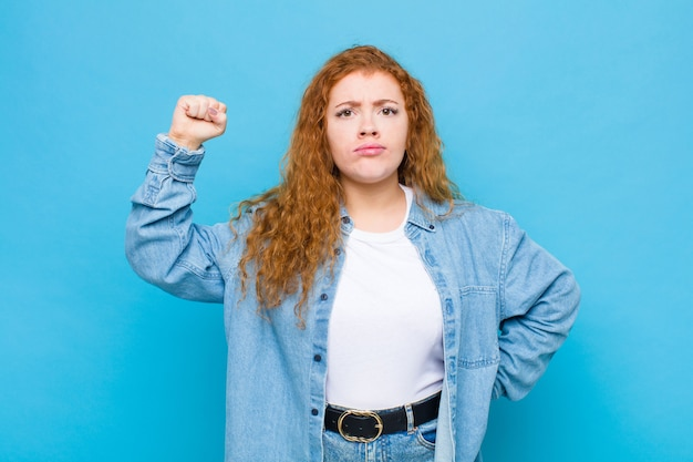 深刻な、強くて反抗的な、拳を上げる、抗議または水色の壁に対する革命のために戦う若い赤い頭の女性