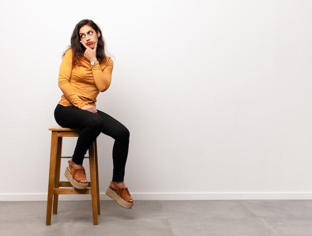 部屋に座っている歯科医を探して、頬を押し、痛みを伴う歯痛、病気、悲惨、不幸に苦しんでいる若いきれいな女性