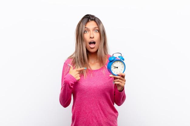 目を覚まし時計を保持している自己を指している、口を大きく開けてショックを受けて驚いた若いきれいな女性。