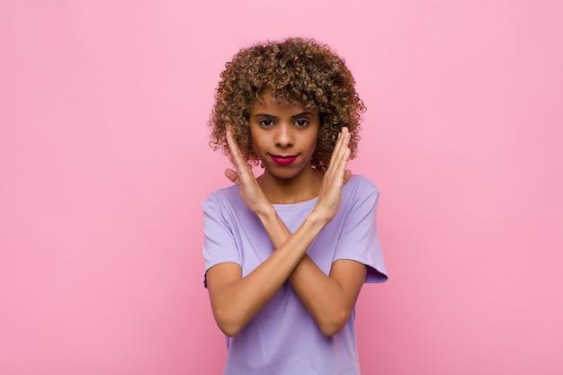あなたの態度にイライラしてうんざりしている若い女性、十分言って!手が正面を横切り、ピンクの壁に立ち寄るように言う