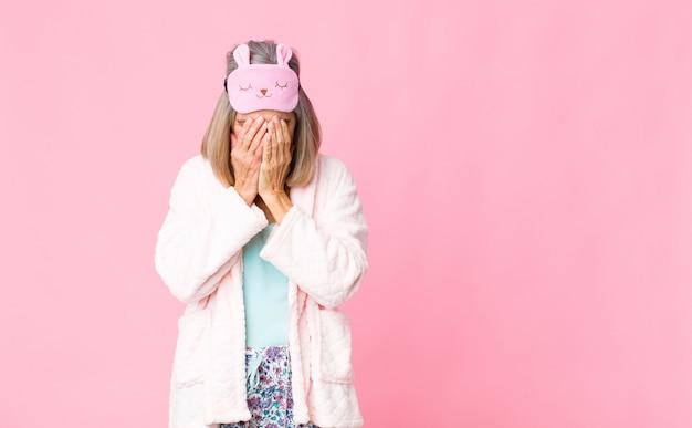 悲しい、欲求不満、緊張、落ち込んでいる中年の女性。両手で顔を覆い、泣いています。ナイトスーツのコンセプト