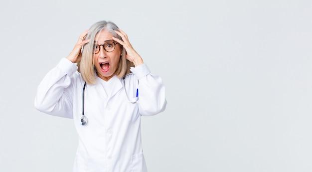 Доктор среднего возраста женщина выглядит возбужденным и удивленным, с открытым ртом обеими руками на голове, чувствуя себя счастливчиком