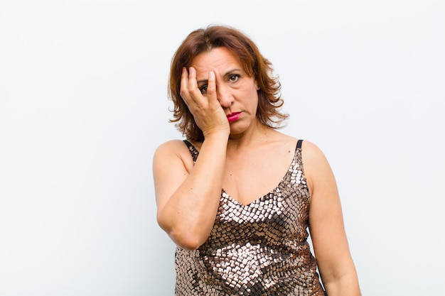 中年のきれいな女性は、白い壁に手で顔を抱えて、退屈で、退屈で退屈な作業の後、退屈、欲求不満、眠気を感じています。