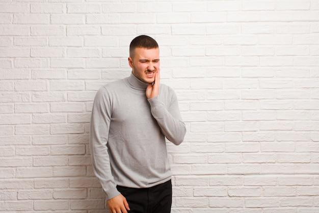 若いハンサムな男の頬を押しながら痛みを伴う歯痛、病気、悲惨、不幸に苦しんで、平らな壁に歯科医を探して