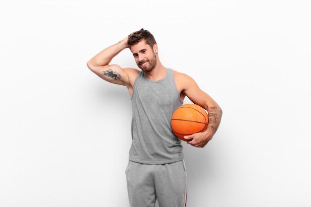 若いハンサムな男が明るく元気に笑みを浮かべて、バスケットボールを保持している肯定的で幸せで自信を持って顔を合わせて頭を抱えています。